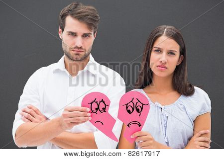 Upset couple holding two halves of broken heart against grey