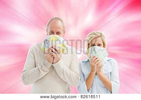 Happy mature couple smiling at camera showing money against digitally generated girly heart design