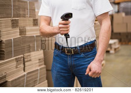 Close up of warehouse worker holding scanner in a large warehouse