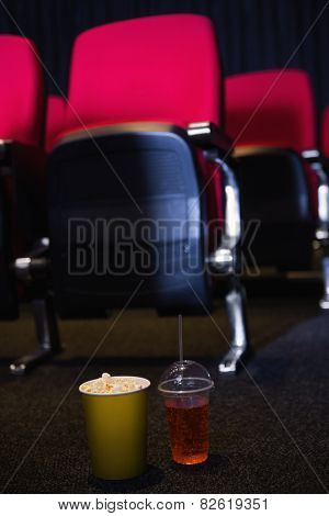 Empty rows of red seats with pop corn and drink on the floor at the cinema