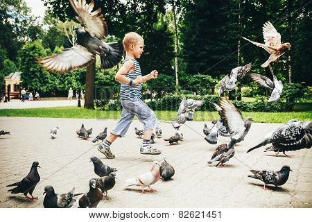 Boy playing with pigeons birds in Gomel park, Belarus