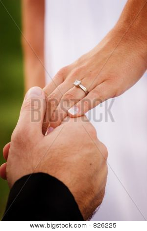 A man holding the hand of a woman showing of the wedding ring.