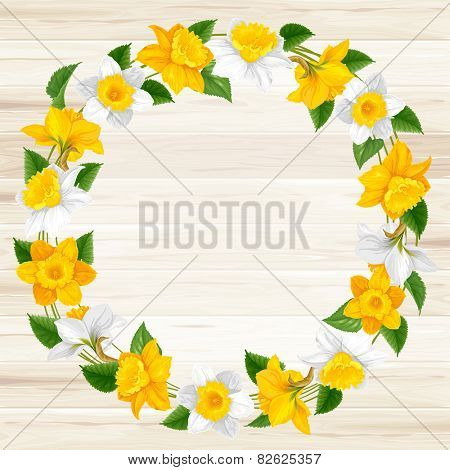 Retro round frame from daffodils flowers on wooden background