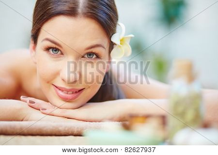 Happy young woman lying in spa salon