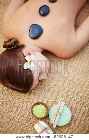 Young girl having relaxing massage with spa stones