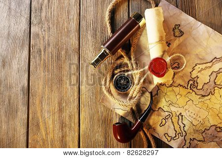 Marine still life spyglass, rope, pipe and world map on wooden background