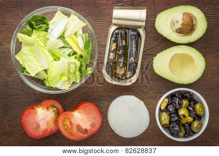 top view of sardine salad ingredients - canned sardines, tomato, romaine lettuce, onion, olives, and avocado