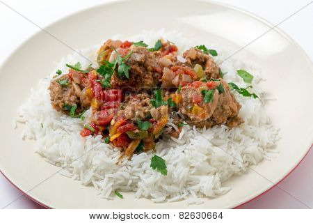 Meatballs Smyrna  cooked with a sauce of cumin, red and yellow capsicums and tomatoes, making a colourful and tasty dish