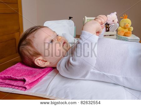 Baby lying playing with a children comb