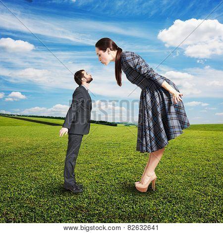 beautiful woman kissing small man. photo at outdoor