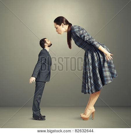 beautiful woman bending forward and kissing small man over dark background