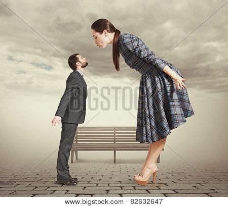 attractive young woman bending forward and kissing small man. photo in park