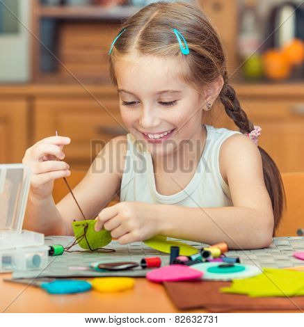 happy cute little girl is engaged in sewing