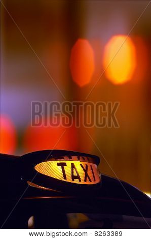 British London Black Taxi Cab Sign At Night With Colorful Background