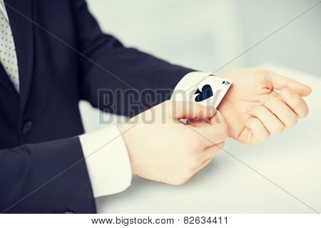 close up of mans hand hiding ace in the sleeve