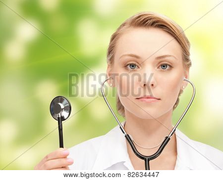 people, medicine, equipment and profession concept - young female doctor with stethoscope over green background