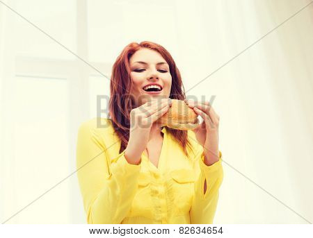 health, eating, food, home and people concept - smiling young woman eating hamburger at home