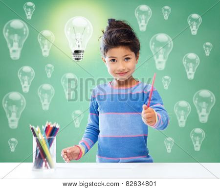 education, school, children, creativity and happy people concept - happy little girl drawing with coloring pencils over green chalk board background and light bulbs