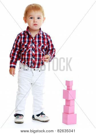 Little boy collects pink pyramid.
