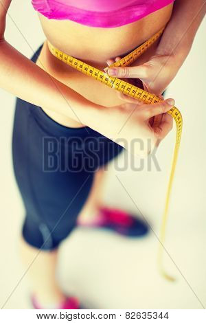 sport and diet concept - trained belly with measuring tape