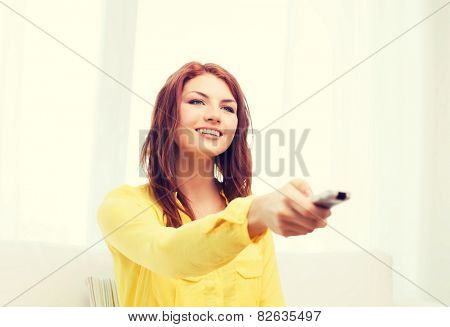 television, relax, home and happiness concept - smiling teenage girl sitting on couch with tv remote control at home