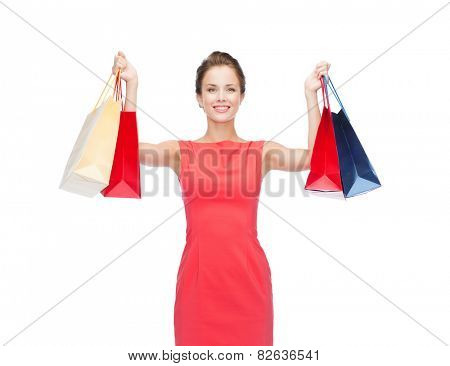 shopping, sale, gifts and holidays concept - smiling woman in red dress with shopping bags
