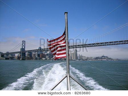 Ondas de bandeira EUA bem-vestida no vento na parte de trás de um Ferry com San Francisco ao fundo