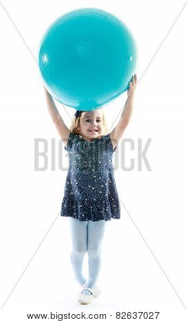 Cheerful little girl raised her head above the big blue ball.