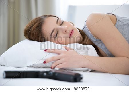 Woman in bed sleeping on the bed with gun