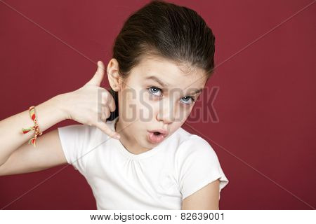 Little Girl making a call me gesture, against background of burgundy wall
