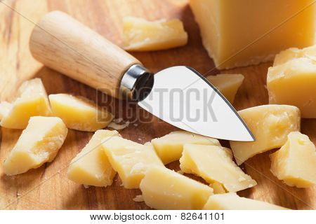 Hard ripened cheese with knife, on wooden board