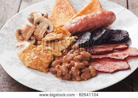 Full english breakfast with eggs, bacon, black pudding, sausage and mushrooms