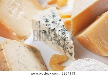 Slice of gorgonzola, blue cheese with other cheeses as background