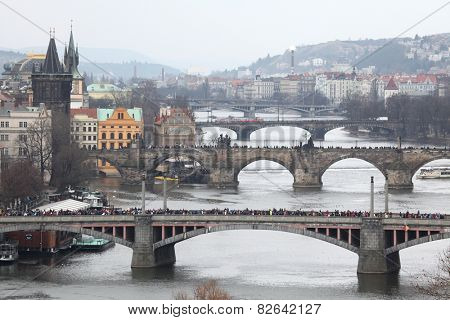 PRAGUE, CZECH REPUBLIC - APRIL 6, 2013: Athletes run over the Manes Bridge on the Vltava River during a marathon run in Prague, Czech Republic. The Charles Bridge is seen in the background.