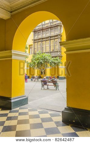 LIMA, PERU, MAY 23, 2014: People rest on bench near Plaza Mayor - view from the arcades of the Municipal Palace of Lima