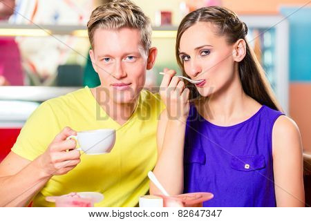 Couple sitting together with coffee and dish of ice cream in ice cream parlor or cafe
