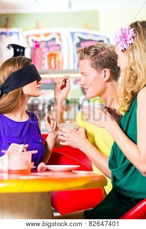 Friends tasting ice-cream with bond eyes, guessing taste in ice cream parlor or cafe