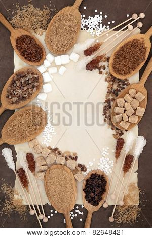 Brown and white sugar in oak wood spoons with crystal lollipops over parchment and brown paper background.