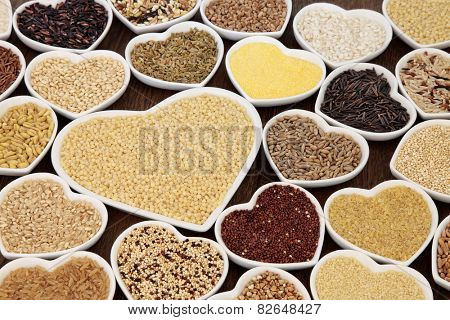 Large cereal and grain food selection in heart shaped porcelain bowls over lokta paper background. Pearl couscous in large dish.