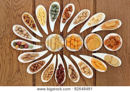 Savoury snack party food selection in porcelain dishes over oak background.