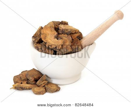 Rhubarb root herb used in chinese herbal medicine in a stone mortar with pestle over white background. Da huang. Rheum palmatum.