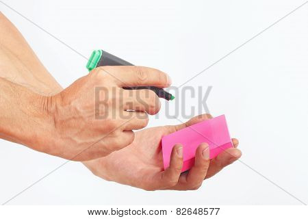 Hand written notes in green marker on a red sticker on white background