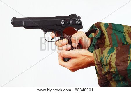 Hands in camouflage uniform with automatic army pistol