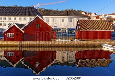 Red Old Buildings On The Mirror Image In The Water