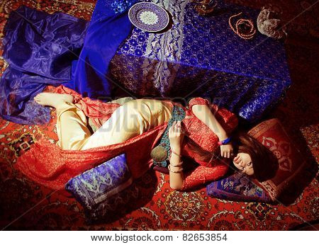 young pretty asian girl in bright colored interior on carpet