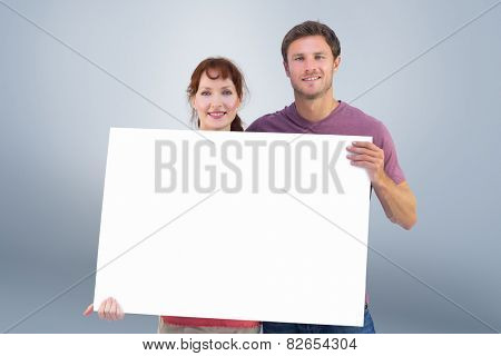 Couple holding a white sign against grey vignette