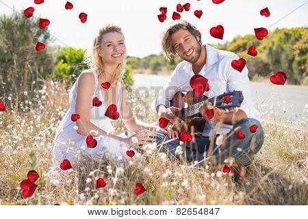 Handsome man serenading his girlfriend with guitar against valentines heart design