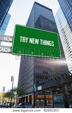 The word try new things and green billboard sign against skyscraper in city