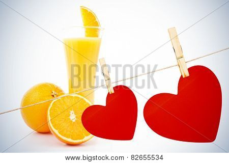 Hearts hanging on a line against one orange and a half next to a glass of orange juice