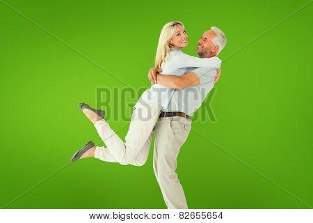 Man picking up his partner while hugging here against green vignette
